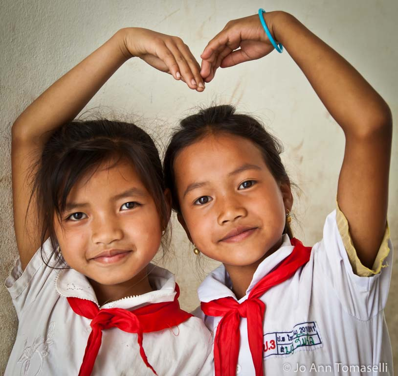 A portrait  photograph by Award Winning Photographer Jo Ann Tomaselli of two schoolgirls in Laos wearing white shirts and red scarves show that they're best friend by linking their hands and forming a heart around themselves. Buy Best Fine Art Photography at  http://jo-ann-tomaselli.artistwebsites.com/