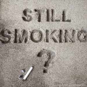 The question 'Still Smoking?' are block printed in sand with a question mark and a cigarette butt nearby.  Best Buy this Image Art  at http://jo-ann-tomaselli.artistwebsites.com/featured/still-smoking-image-art-jo-ann-tomaselli.html