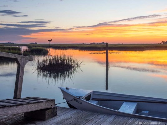 A small boat tied to a dock at sunrise for-sale online